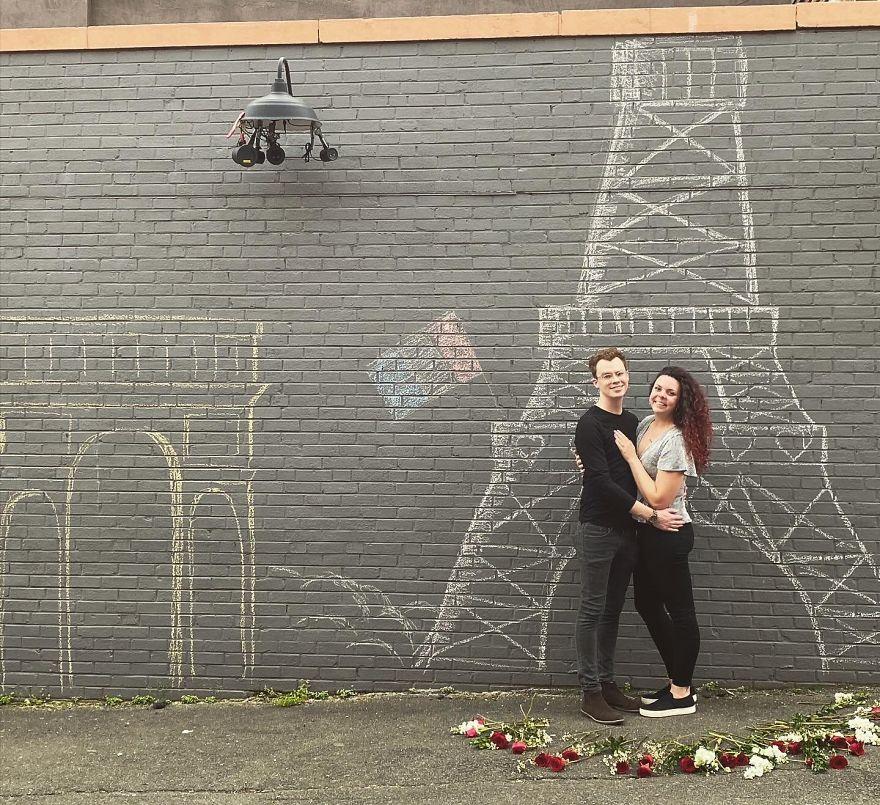 Το ζευγάρι Luke και Erika μπροστά στον τοίχο με τον σχεδιασμένο από κιμωλία Πύργο του Άιφελ